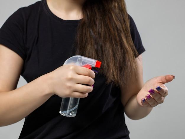 特別なスプレーで手を洗う黒いtシャツの女性