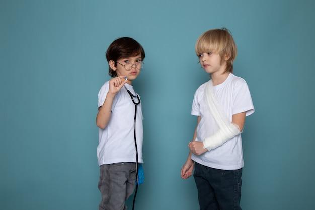 若い子供たちかわいい甘い白いtシャツとジーンズに青い机の上