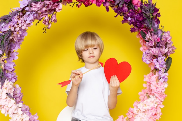 花の上に座ってハートの形をした白いtシャツを着た正面の金髪の子供が黄色のスペースに立った