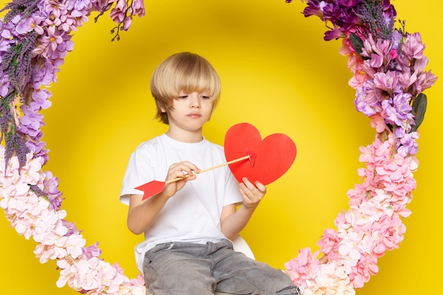黄色の床に作られた花の机の上にハートの形を保持している白いtシャツでかわいい愛らしい正面金髪の少年