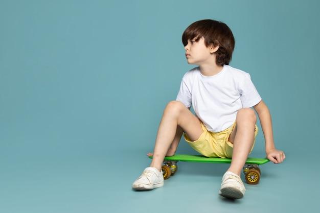青いスペースで白いtシャツに乗ってスケートボードでかわいいかわいい男の子の正面図