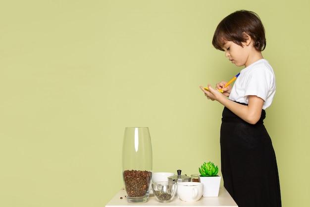 石の色の机の上のテーブルでコーヒードリンクの準備を書き留めて白いtシャツで正面のかわいい男の子
