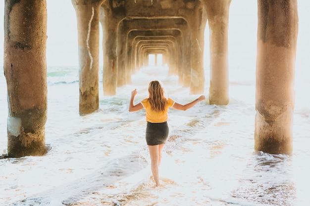 大きな石の桟橋の下に立っている黄色のtシャツとショートパンツの魅力的な女性