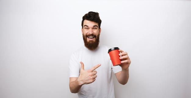 コーヒーや紅茶の赤い紙コップを押しながら白いtシャツで白い背景にそれを指しているひげを生やした男。