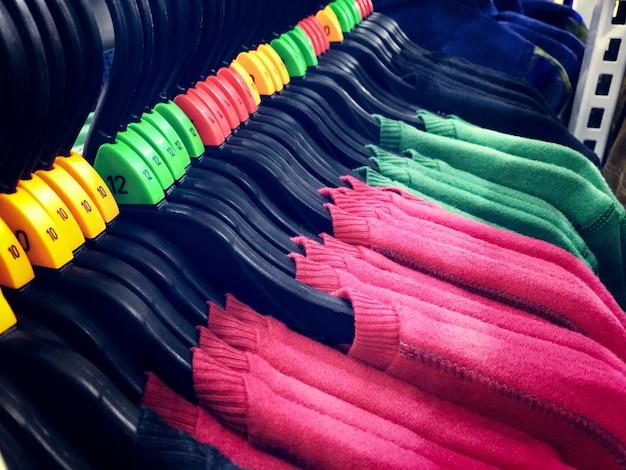 赤と緑のtシャツ、ハンガー、サイズ番号ラベル付き
