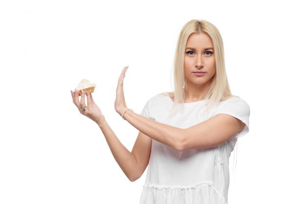 ダイエット。ダイエットのコンセプト。健康食品。白いtシャツの若いブロンドの女性は、おいしいケーキで手が止まる