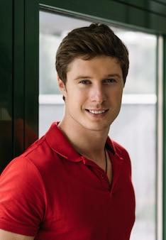 写真のポーズ、笑みを浮かべてカジュアルな赤いtシャツを着ている若いハンサムな男