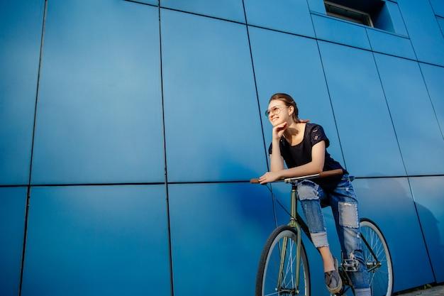 屋外で自転車で歩きながら楽しんで、ジーンズとtシャツを着てサングラスでファッショナブルな女の子。