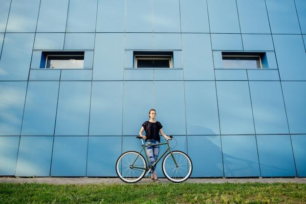 青い壁の建物に対して自転車でデニムとtシャツの立っているファッショナブルな女の子の完全な長さのビュー。レジャーのコンセプトです。