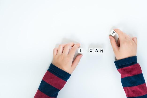 幼児の手が「できない」から「できる」の文字から「t」の文字が入ったプラスチック製の立方体を取り除くことにしました