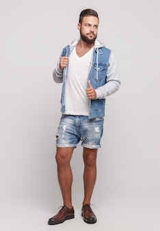 シンプルなグレーのスペースにデニムジャケットの美しいひげ、白いtシャツ、デニムのショートパンツを着たスタイリッシュな若い陽気な男。看板のデニムジャケットとデニムショーツの広告コンセプト。