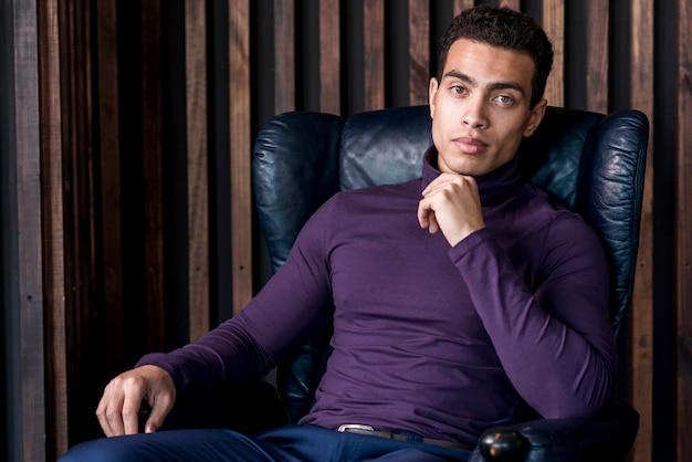 カメラ目線の肘掛け椅子に座っているポロ首tシャツでハンサムな若い男