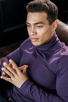紫色のポロの首のtシャツで熟考されたハンサムな若い男のクローズアップ