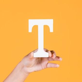 黄色の背景の上に大文字のt文字を示す女性の手のクローズアップ