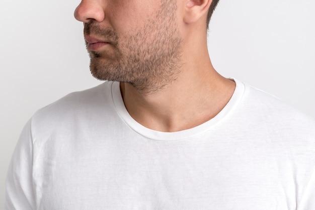 白いtシャツの無精ひげの若い男のクローズアップ