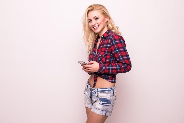 赤いtシャツとピンクに分離された短いジーンズでブロンドの女の子