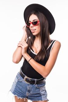 Tシャツショートパンツとサングラスのポーズのきれいな女性。