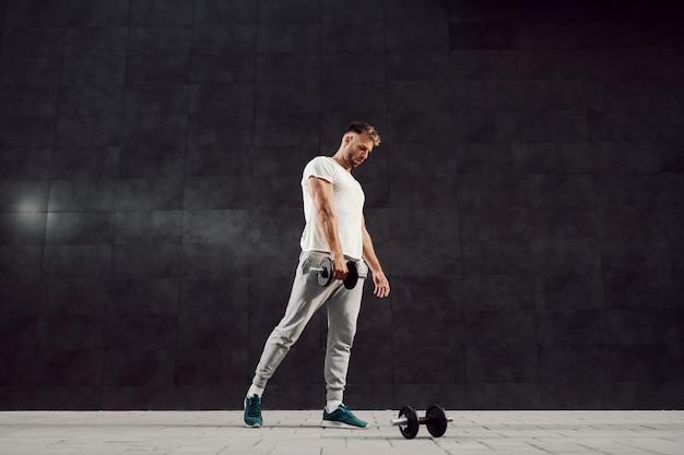 灰色の壁の前に立っているとダンベルを保持しているtシャツとトラックスーツで魅力的な白人筋肉ひげを生やした金髪男の完全な長さ。