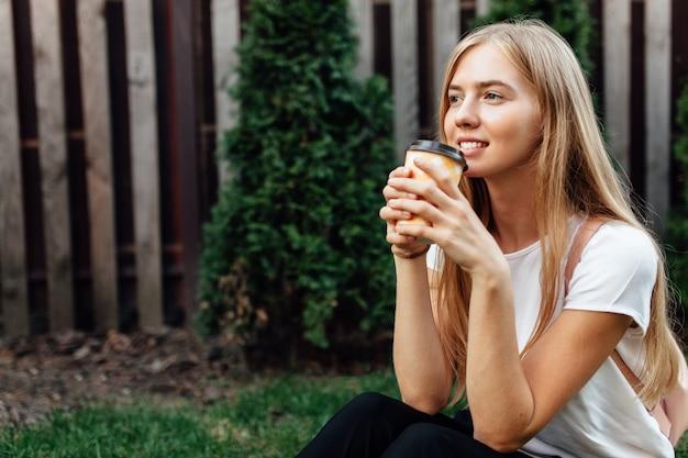 屋外で白いtシャツを着た若者の肖像画。芝生の上に座ってコーヒーを飲む女の子。