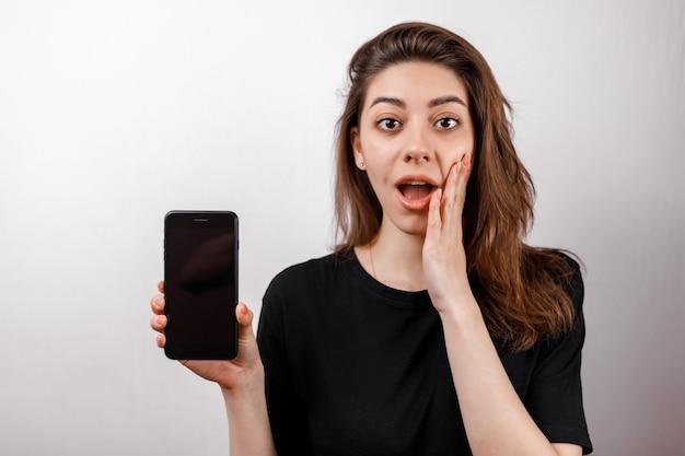 笑顔の黒いtシャツの若いブルネットの女性は白の携帯電話を示しています