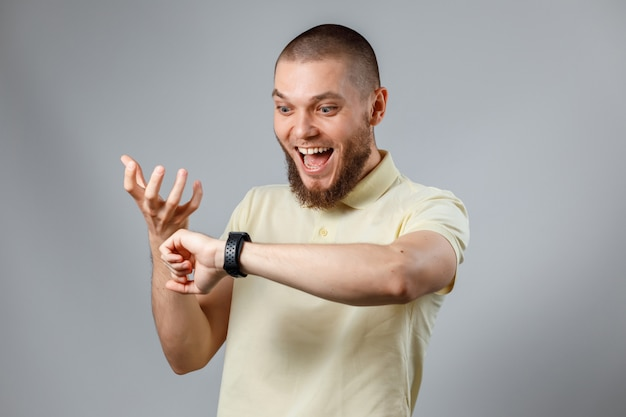 黄色のtシャツを着た若い男性の肖像画が灰色で時計を見てください。