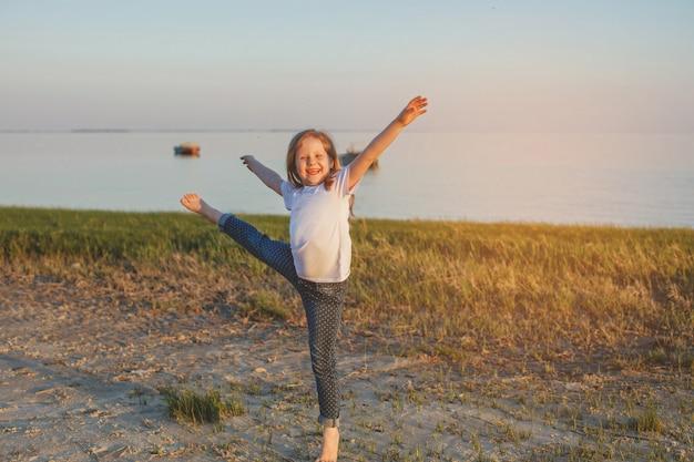 ジーンズの女の子と夏にビーチで裸足で踊るtシャツ