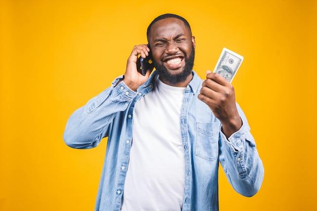 勝者!お金のドル札と驚きの携帯電話を保持しているカジュアルなtシャツの若い金持ちのアフリカ系アメリカ人