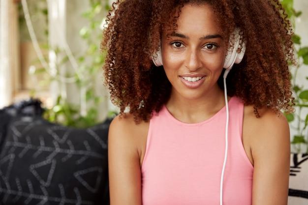 自信を持っている暗い肌の魅力的なアフリカ系アメリカ人の女性はピンクのカジュアルなtシャツを着ており、ヘッドフォンでオンラインで曲を聴いています。人、テクノロジー、ライフスタイル