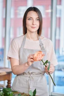 花屋で働いている間白いtシャツとエプロンのバラの束を作るのはかなり若い女性