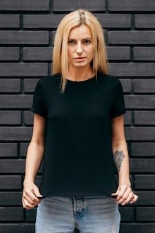黒い壁の背景にポーズ黒いtシャツを着てスタイリッシュなブロンドの女の子