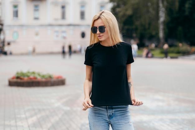 黒のtシャツと眼鏡のストリートに対してポーズを着てスタイリッシュなブロンドの女の子