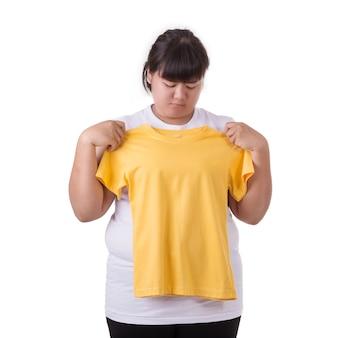 ファットアジアの女性は、黄色のtシャツの小さなサイズを着用しようとしている