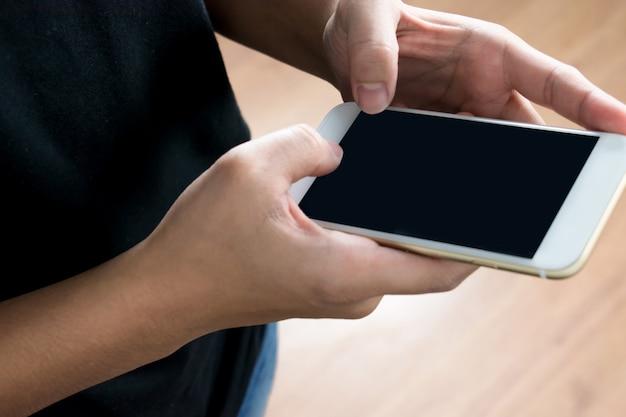 黒いtシャツを着ている実地の人々は、電話で何かを見つけるために技術を使っています。