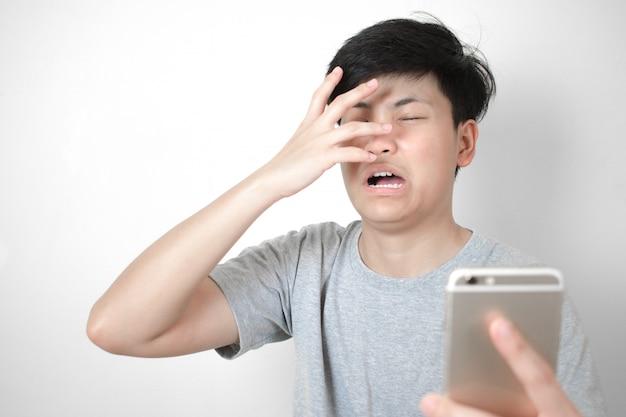 アジア人はグレーのtシャツを着ており、スマートフォンにショックを受けています。