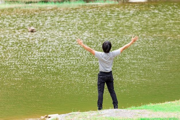 川の横に立っているカーゴパンツとtシャツを着た幸せな男