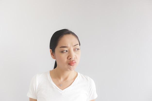 白いtシャツを着た女性の不機嫌そうな不機嫌そうな表情。腹を立てていて不気味な概念。
