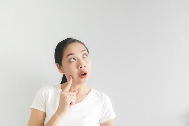 白いtシャツで幸せな女は、アイデアを見つけ、空の背景を見ています。