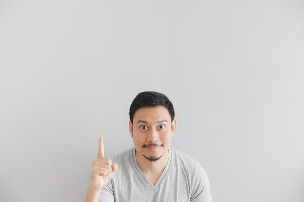 手で灰色のtシャツの男の幸せそうな顔は、空のスペースをポイントします。