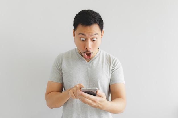 灰色のtシャツを着た男のすごい顔は、スマートフォンに驚かされます。