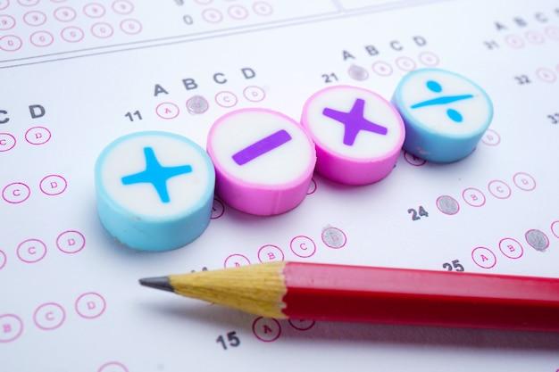 解答シートの背景にある数学記号と鉛筆:教育研究数学学習t
