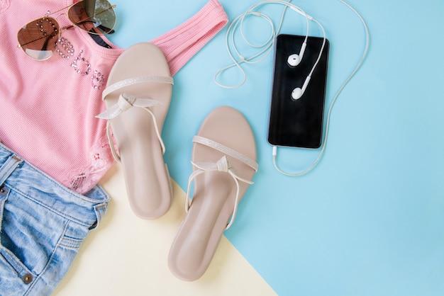 カジュアルな婦人服とアクセサリー。ピンクのtシャツ、夏のサンダル、青いデニムのショートパンツ、おしゃれなサングラスのスマートフォン