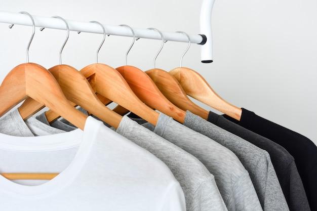 木製の洋服ハンガーに掛かっている黒、グレーと白のtシャツのコレクションを閉じる