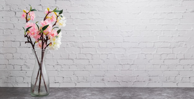 白いレンガ壁tに乾燥した桜の花のガラス鍋