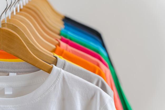 ハンガー、アパレルの背景にカラフルなtシャツのクローズアップ