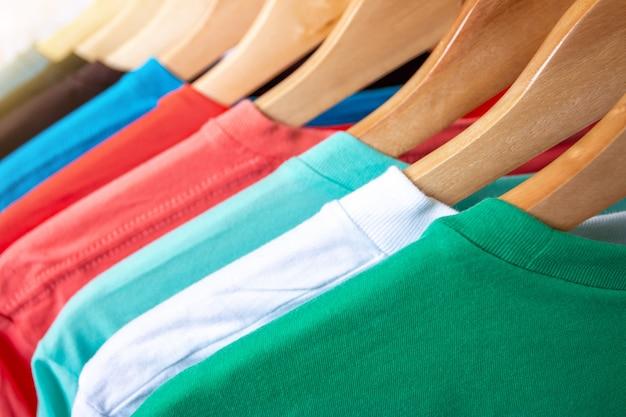 衣類ラックのファッションtシャツ-店のクローゼットの木製ハンガーに明るいカラフルなクローゼットのクローズアップ。