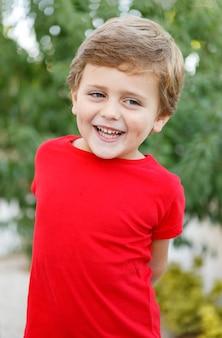 庭に赤いtシャツと幸せな子供