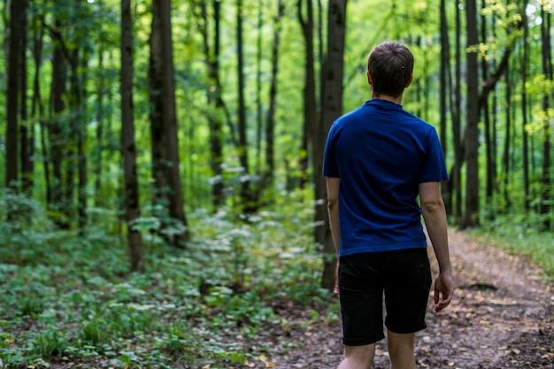 青いtシャツの若い男が歩くし、秋の森の周りに見える