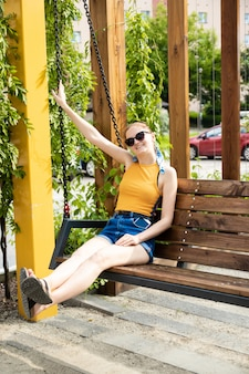 黄色のtシャツとショートパンツの若いブロンドの女の子は金属チェーンと木製のブランコに乗っています。