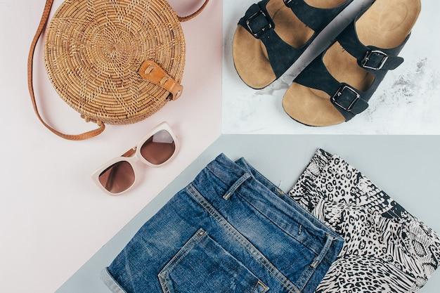 アニマルプリントtシャツ、ブルーデニムショートパンツ、ファッショナブルなラタンバッグ、サングラス。
