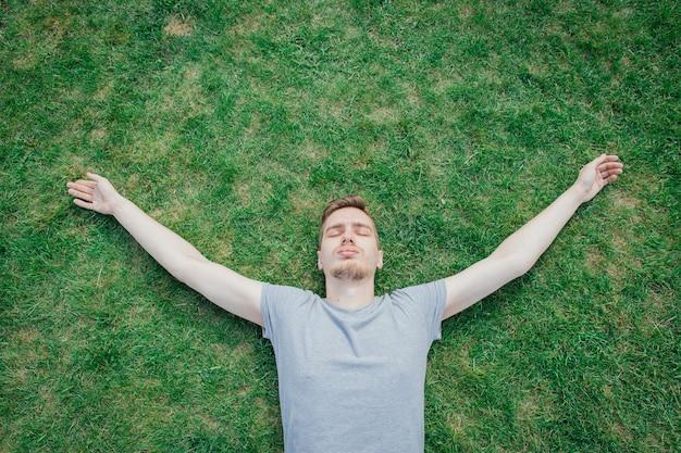 緑の草、夏に横たわっている灰色のtシャツの男。安静時の男